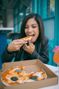 photo of woman eating pizza